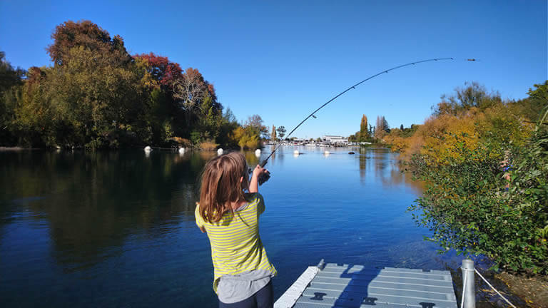 Kids fish for trout from Riverside Apartment Taupo
