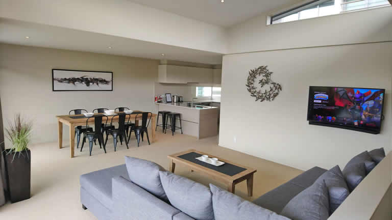 Apartment One dining and living area with views over the Waikato river